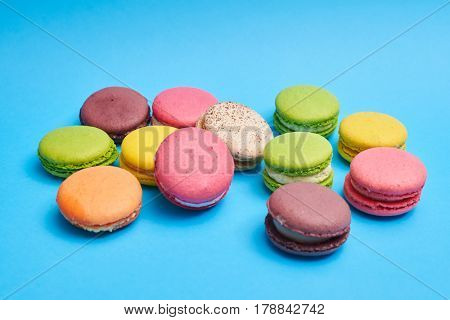 Homemade macaroons lying on a blue flatlay. Set of different french cookies macaroons