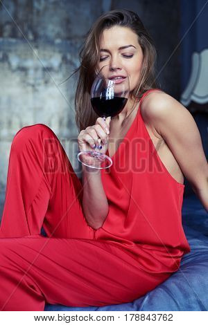 Close-up shot of an alluring brunette drinking red wine from a glass. Female in a red overall sitting on the bed. Gorgeous lady spending time at home