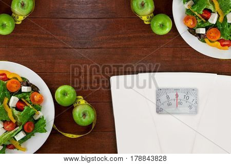 weighting scale against salad with apples and measuring tape on table