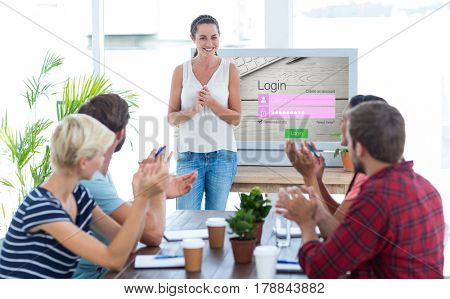 Colleagues clapping hands in a meeting against close-up of login page