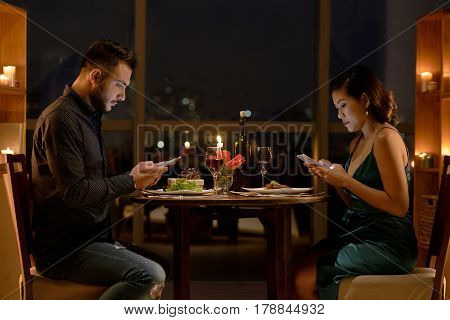 Young people checking their smartphones during romantic date in restaurant