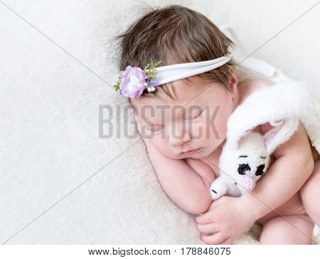 Small girl wrapped with a blanket sleeping with her white bunny with big ears