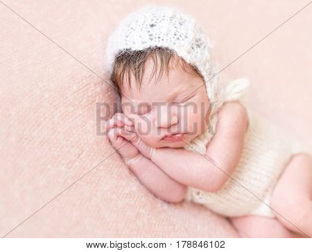 Adorable newborn girl in a lovely hat and in a costume napping on her side