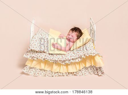 Adorable hairy baby sleeping in the adult-like bed with colorful sheets, covered with blanket