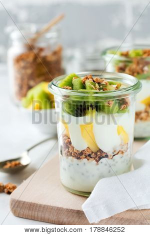 Yogurt granola parfait with mangokiwi tropical fruits аnd сhia seeds layered dessert or breakfast. Selective focus.