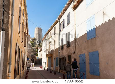 Gruissan, France - October 11, 2016;  Tourists wander narrow shady streets between buildings of Medieval Mediterranean town Barbarossa's castle tower at street end Gruissan France.