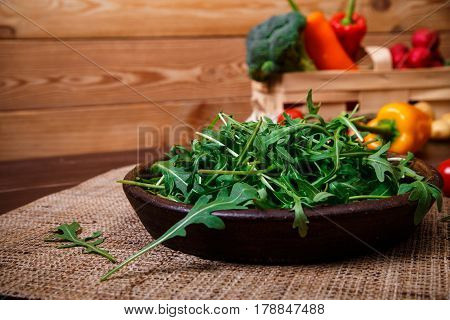 Arugula leaves in bowl. Fresh salad. Pepper and brocoli. Natural raw vegetables. Organic bio food on rustic wooden table.