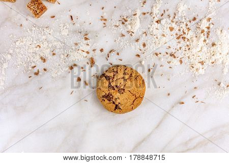 The process of making chocolate chip cookies. Overhead shot of biscuits with grated chocolate, cane sugar, flour, and copy space