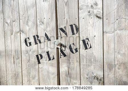 close-up on a beach wooden trunk where it is written in French: Grand Plage or big beach