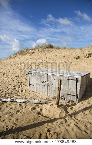 sandy beach in Vendee France with blue sky and white clouds and a storing wooden trunk on which is written Grand Plage meaning main beach in French