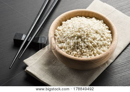 wooden bowl with rice and japanese chopsticks on black wooden table