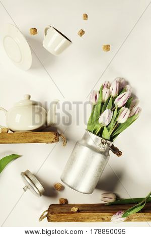 Flying pink tulips in aluminium milk can and tea cup against white wall