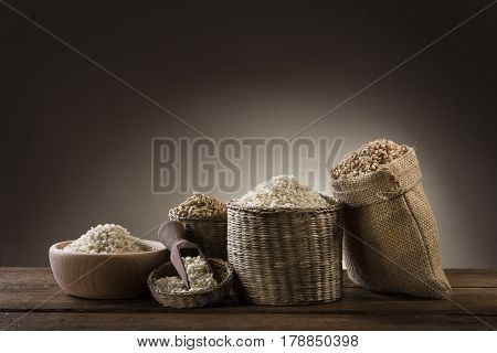 variety of different rice in rustic bowl and bags on wooden table