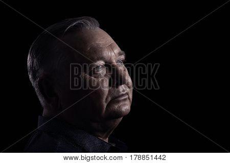 Close up portrait of aged man wearing shirt against black background - retirement concept, copy space