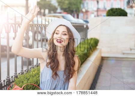 Charming smiling young woman sitting and waving to someone in the city street