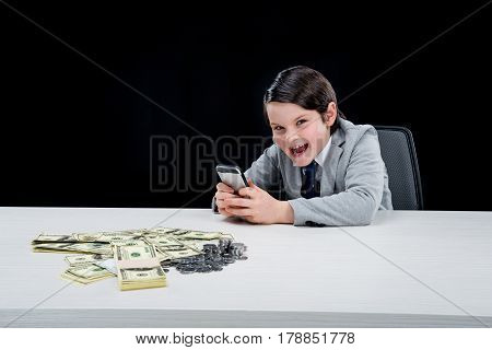 Portrait Of Cunning Boy Playing Businessman And Using Smartphone On Black