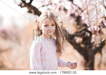 Smiling kid girl 4-5 year old holding peach flower in peach orchard. Looking at camera. Childhood.