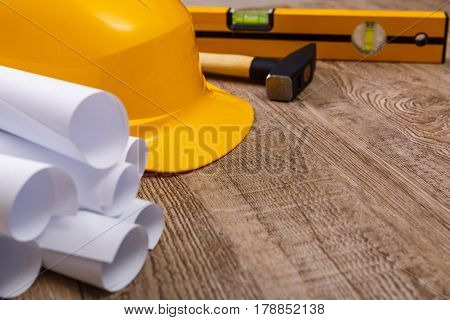 Helmet, hammer and building level. Architecture plans. Construction design. Wood rustic background.
