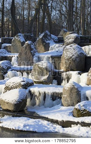 Snow-covered boulders in the cascade thaw in the icy system of reservoirs Tsarskoye Selo (St. Petersburg).