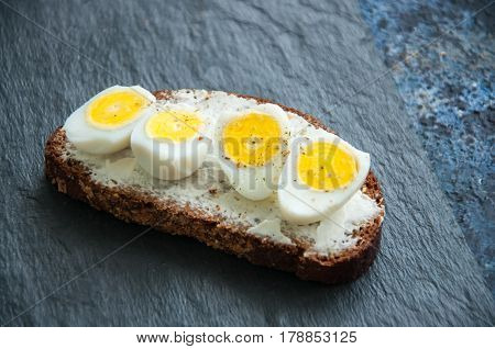 Rye Bread Bruschetta.  Quail Eggs And Cream Cheese Sandwich Served On A Stone Board On Blue Backgrou
