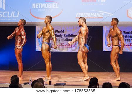 MAASTRICHT THE NETHERLANDS - OCTOBER 25 2015: Male bodybuilders flex their muscles and show their best physique in a side pose on stage at the World Grandprix Bodybuilding and Fitness of the WBBF-WFF