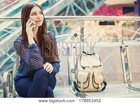 Young caucasian woman is sitting at an airport and speaking by her phone.a