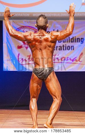 MAASTRICHT THE NETHERLANDS - OCTOBER 25 2015: Male bodybuilder flexes his muscles and shows his best back pose at the World Grandprix Bodybuilding and Fitness of the WBBF-WFF
