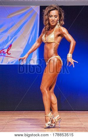 MAASTRICHT THE NETHERLANDS - OCTOBER 25 2015: Female physique model Esther Blom shows her best side pose at championship on stage at the World Grandprix Bodybuilding and Fitness of the WBBF-WFF