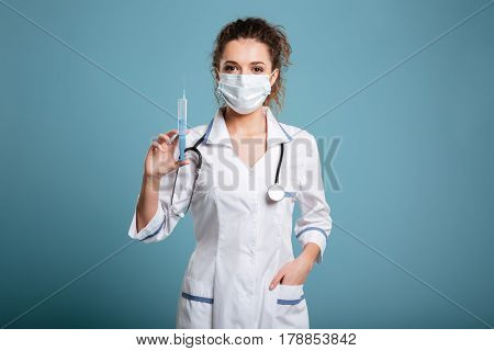 Portrait of a female doctor or medical nurse in face mask and lab coat holding syringe isolated on blue background