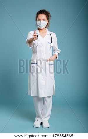 Full length portrait of a confident female doctor or nurse wearing surgical mask and showing thumbs-up isolated on blue background