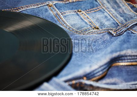 retro vinyl disk and blue jeans on background