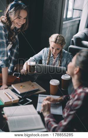 Beautiful girls students drinking coffee and studying together at desk
