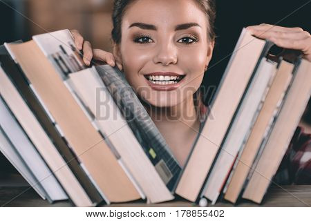 Smiling young woman student choosing book on bookshelf