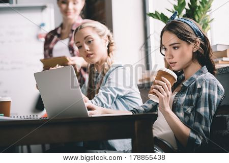 Attractive young women students studying together with laptop