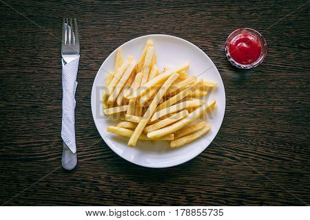 French fries on a white plate with ketchup on a wooden table with cutlery