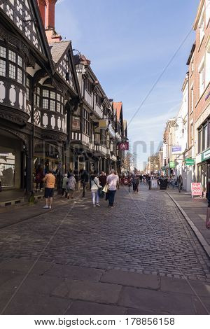 Chester England UK - March 25 2017: Shoppers and visitors on Northgate Street with its cobble stone pavements and beautiful half timbered buildings in the historic city of Chester