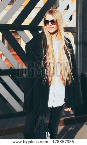 Young long hair blond woman in sunglasses and a fashionable outfit posing on the street warm spring evening. Fashion blogger. Streetstyle.