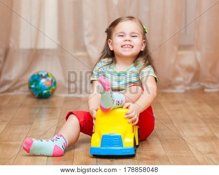 Child girl playing with a toy car on floor at home
