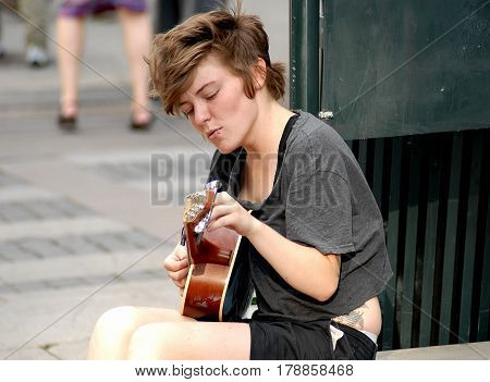 Oslo Norway - July 22 2014: street musician performing on the main street Karl Johans Gate. This street is one of the busiest of the city full of shops bars hotels and terraces.