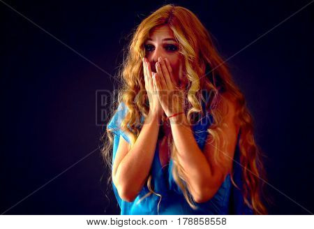 Shocked woman screaming with joyful. Surprised excited happy girl in light dress shouting with joy or fright and cuddle her hands to her cheeks. Black friday holiday deals on dark background.