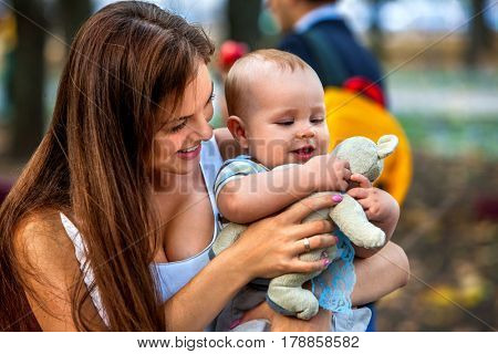 Baby in park outdoor. Kid with toy on mom's hands. Happy beautiful mom and child summer sunrise or sunset on city outside. Portrait of happy loving mother and her son spring outdoors .