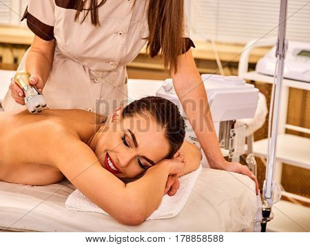 Woman back massage beauty salon. Electric stimulation female skin care . Professional equipment microcurrent body lift . Anti aging rejuvenation . Receiving electroporation beauty therapy indoor.