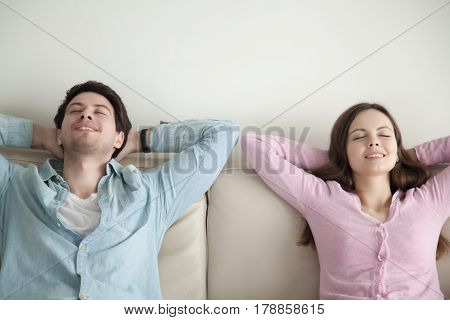 Happy young couple enjoying sitting on sofa at home, resting hands behind the head, relaxing with eyes closed, lounging and recreating, dreaming of vacation, imagining, listening to music, lazy day
