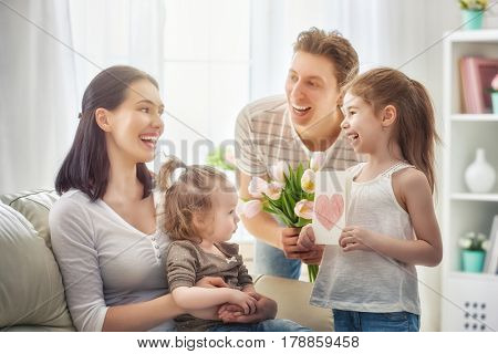 Happy mother's day! Two children daughters with dad congratulate mom and give her a postcard and flowers tulips. Mum and girls smiling and hugging. Family holiday and togetherness.
