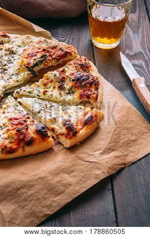 Whole And Slices Of White Pizza On A Parchment Paper With Glass Of Beer On A Wooden Background.