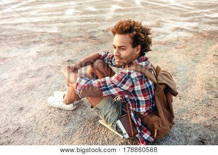 Handsome thoughtful african young man with backpack sitting and thinking