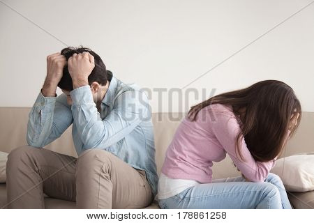 Man and woman feeling stressed and angry at each other, frustrated couple sitting back to back, hands on head, not talking after dispute, teenagers quarrel, family crisis and relationships problems