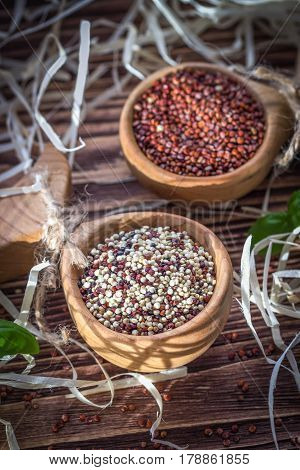 Mixed and red raw quinoa seeds in wooden spoons on a brown background. Rustic style