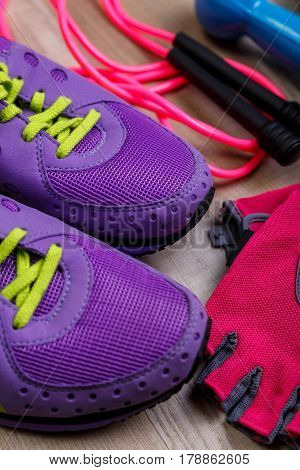 Fitness gym equipment. Sneakers, dumbbells with skipping rope. Workout gloves and footwear. Sport trainers with green shoelace.