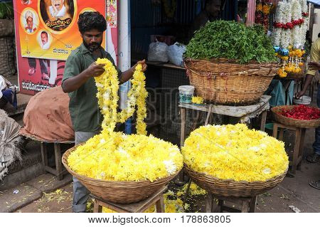 Mysore India - 24 January 2015: Indian vendor selling flowers to the customers in the Devaraja market at Mysore on India
